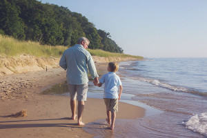dad and son walking hand in hand at beach