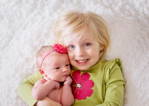 big sister with newborn sister photos