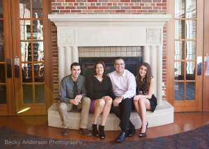family of four in front of fireplace